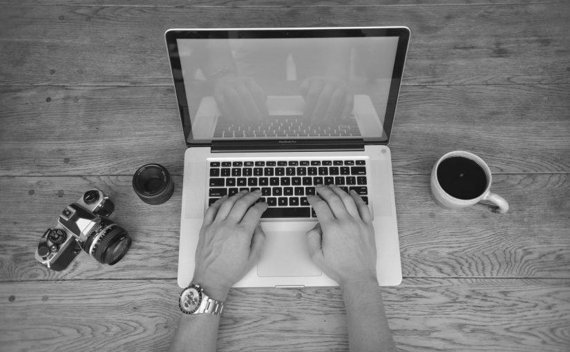 Manos sobre MacBook Pro, café y cámara de fotos